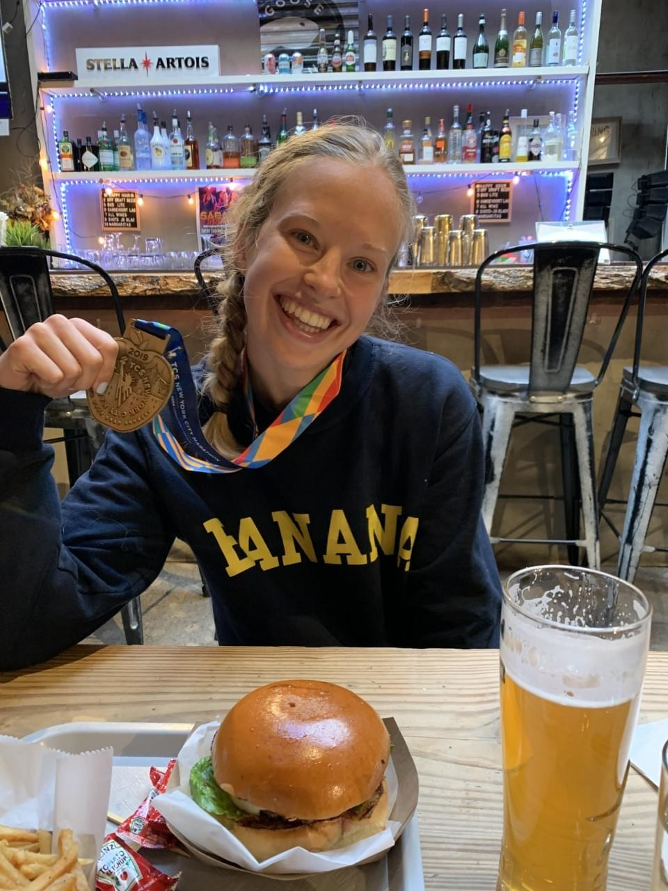 A New York marathon runner celebrates with her medal and a meal after completing the marathon