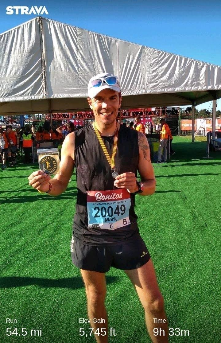 Runner celebrates receiving the Robert Mtshali medal at the finish line of the 2019 Comrades Marathon at Scottsville Racecourse in Pietermaritzburg