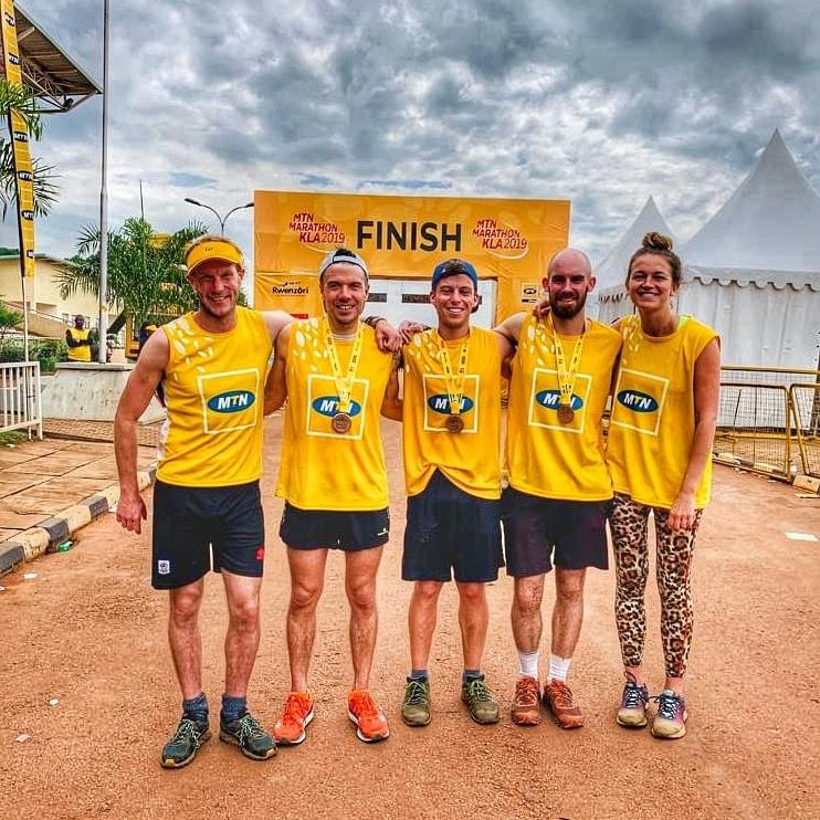 runners celebrate receiving their medal at the 2019 MTN marathon finish in Kampala
