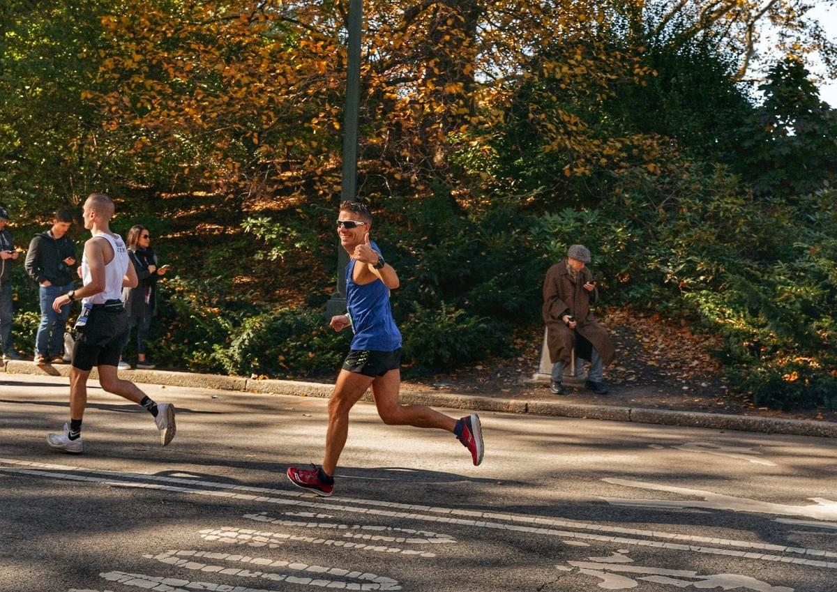 A runner gives a thumbs up whilst passing through Central Park at mile 24 of the New York City marathon