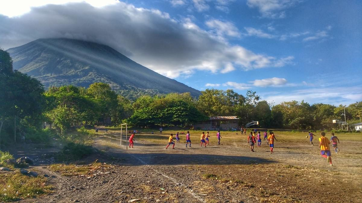 A local football match on a dirt pitch in the shadow of a volcano