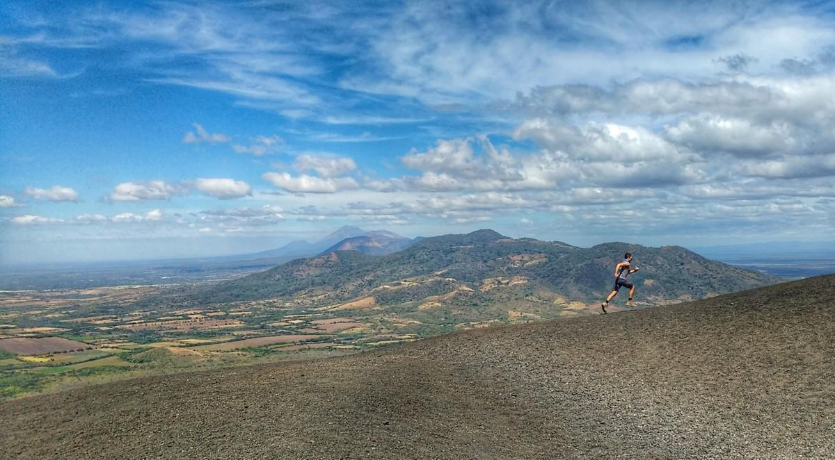 Running the incline of Cerro Negro volcano, in the background, hills as far as the eye can see