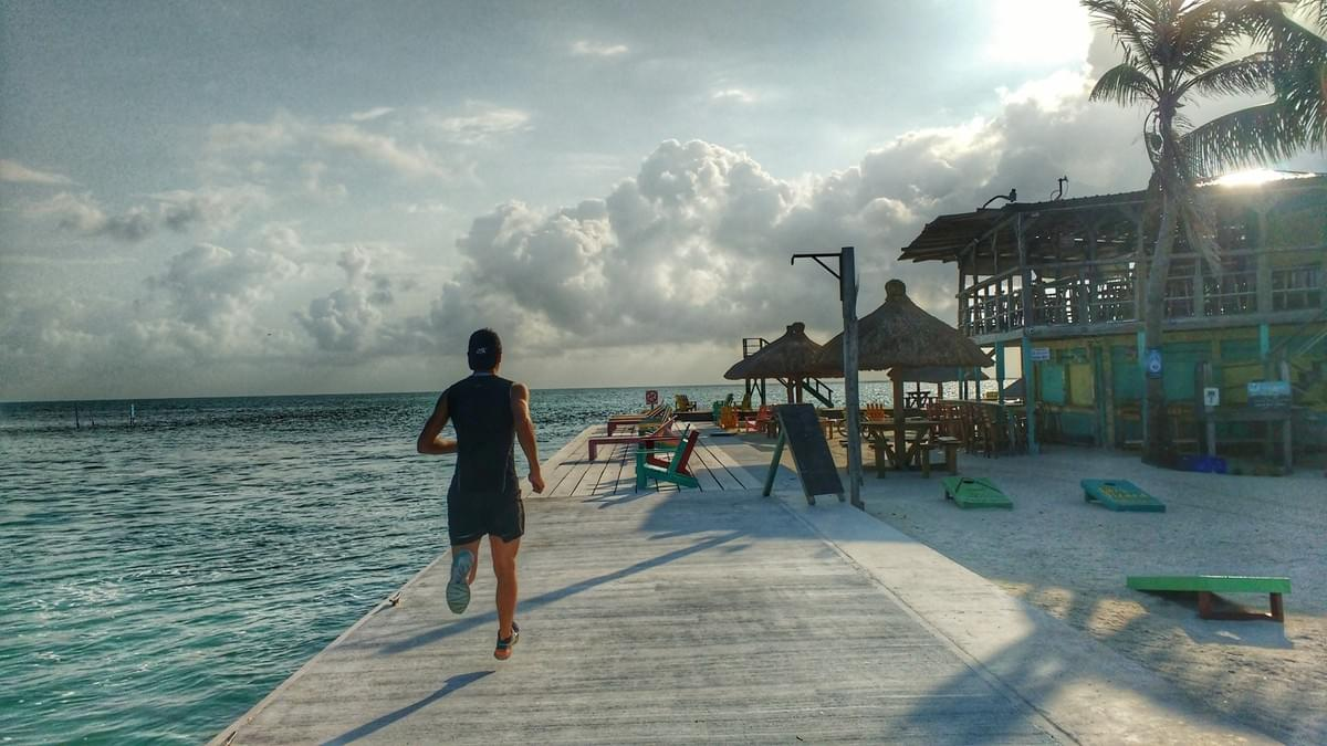 A runner on a boardwalk extending into the sea on the Caribbean island of Caye Caulker, Belize