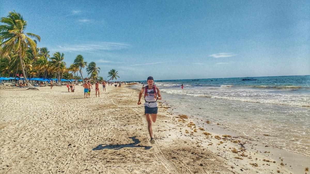 A runner on the beachfront in Tulum, Mexico. Palms and tourists on the left, Caribbean Sea to the right.