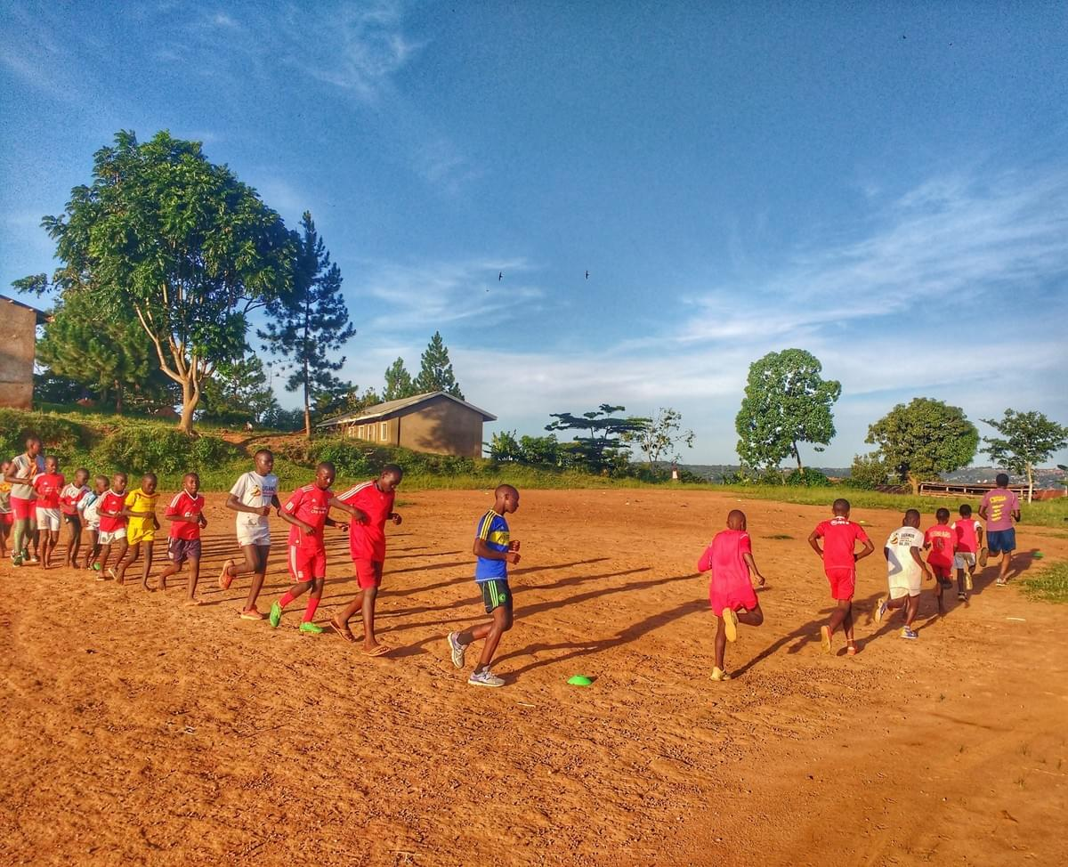 Local children take part in a running session on a dirt pitch in rural Uganda