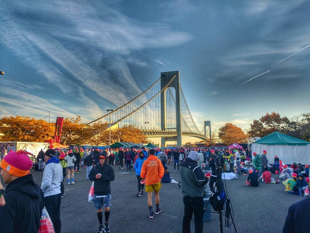Runners walk the New York City Marathon race village at Ford Wadsworth on Staten Island, Verrazano-Narrows Bridge looms large in the background