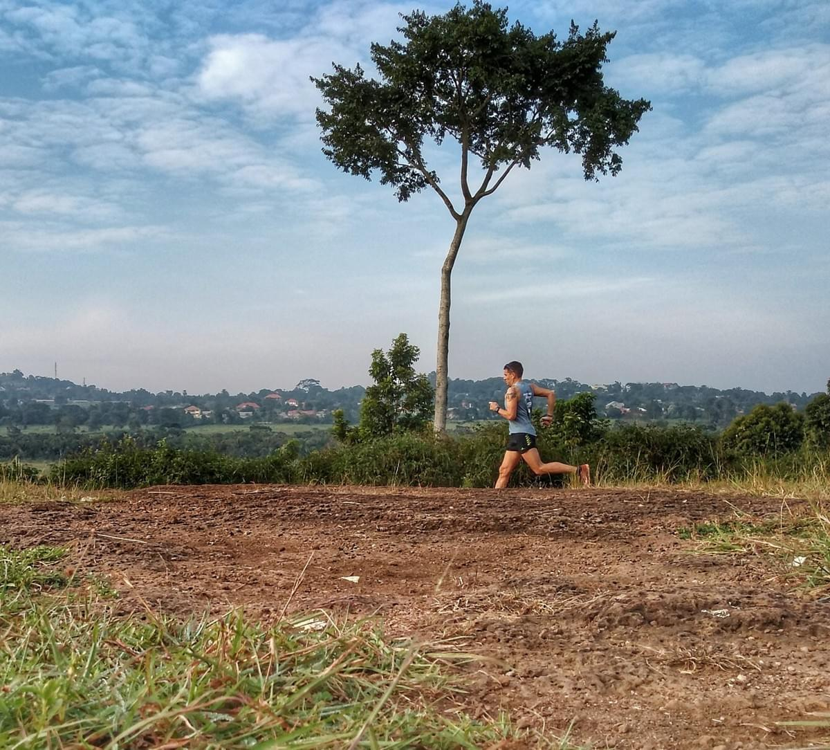 A solo trail runner runs past a large tree in Entebbe, Uganda