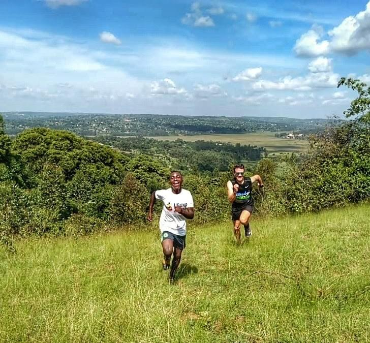 A local boy laughs as he beats a runner on a hill climb on a ridge above lush countryside in Masaka, Uganda