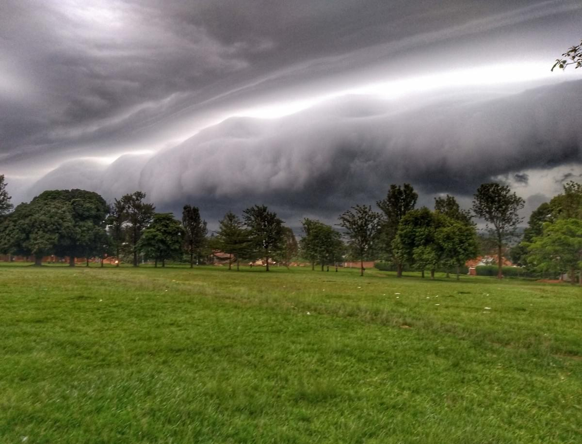 A huge storm front rolls in toward the grass and trees of Liberation Square, Masaka
