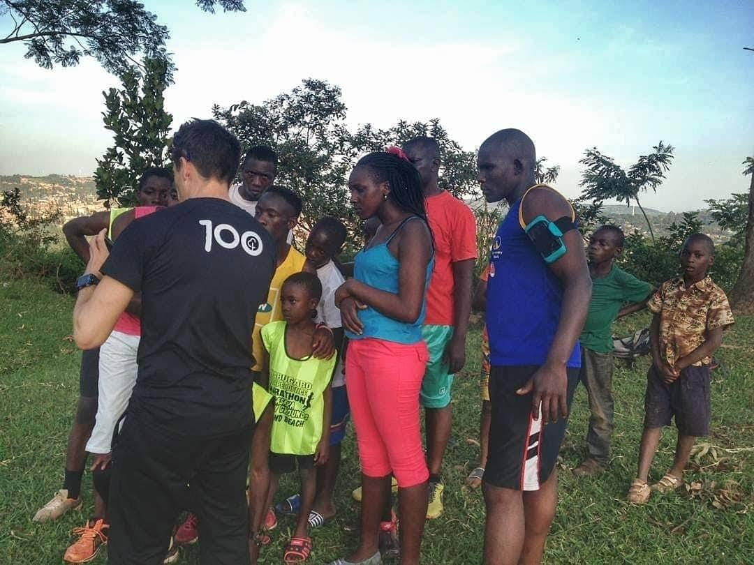 A coach showing video analysis on his phone to a group of local runners in Masaka. Uganda