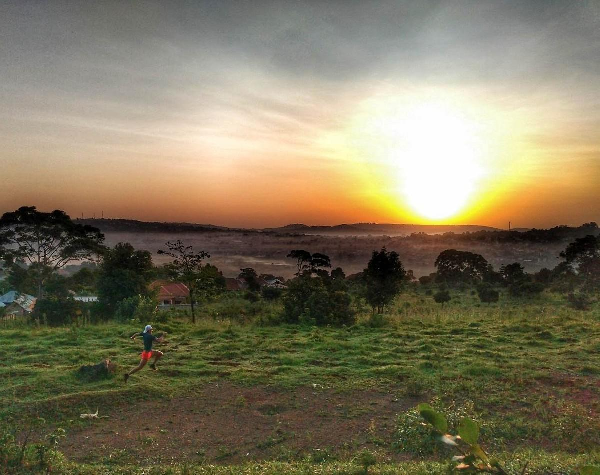 A runner moves across a bumpy meadow during a spectacular sunrise run above a misty Masaka, Uganda