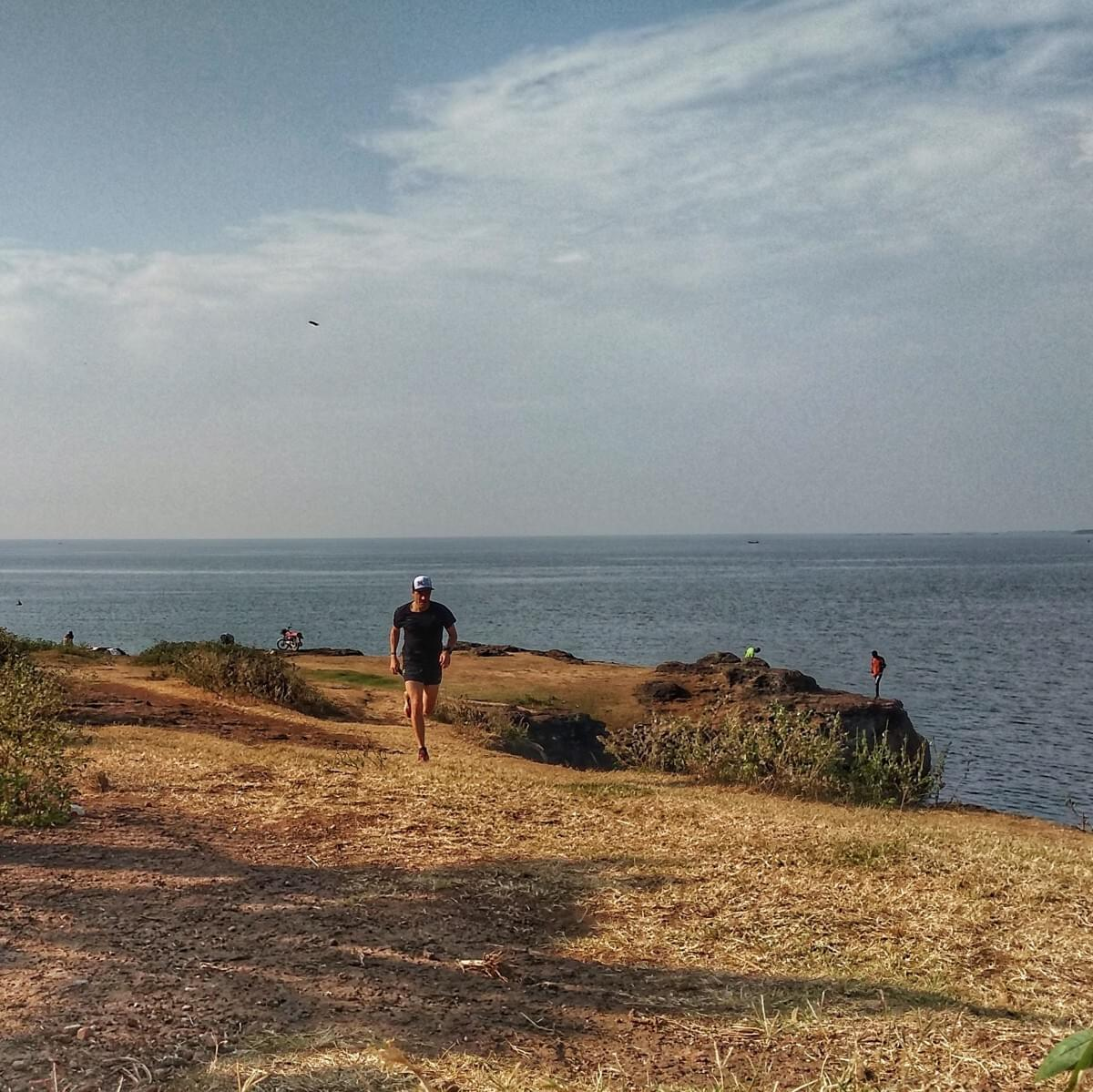 A solo runner climbs a hill on patchy grass above the sprawling Lake Victoria, Entebbe, Uganda