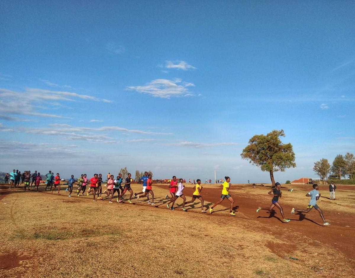 A large group of female Ugandan runners on an interval training session on a thin dirt track in Kapchorwa town
