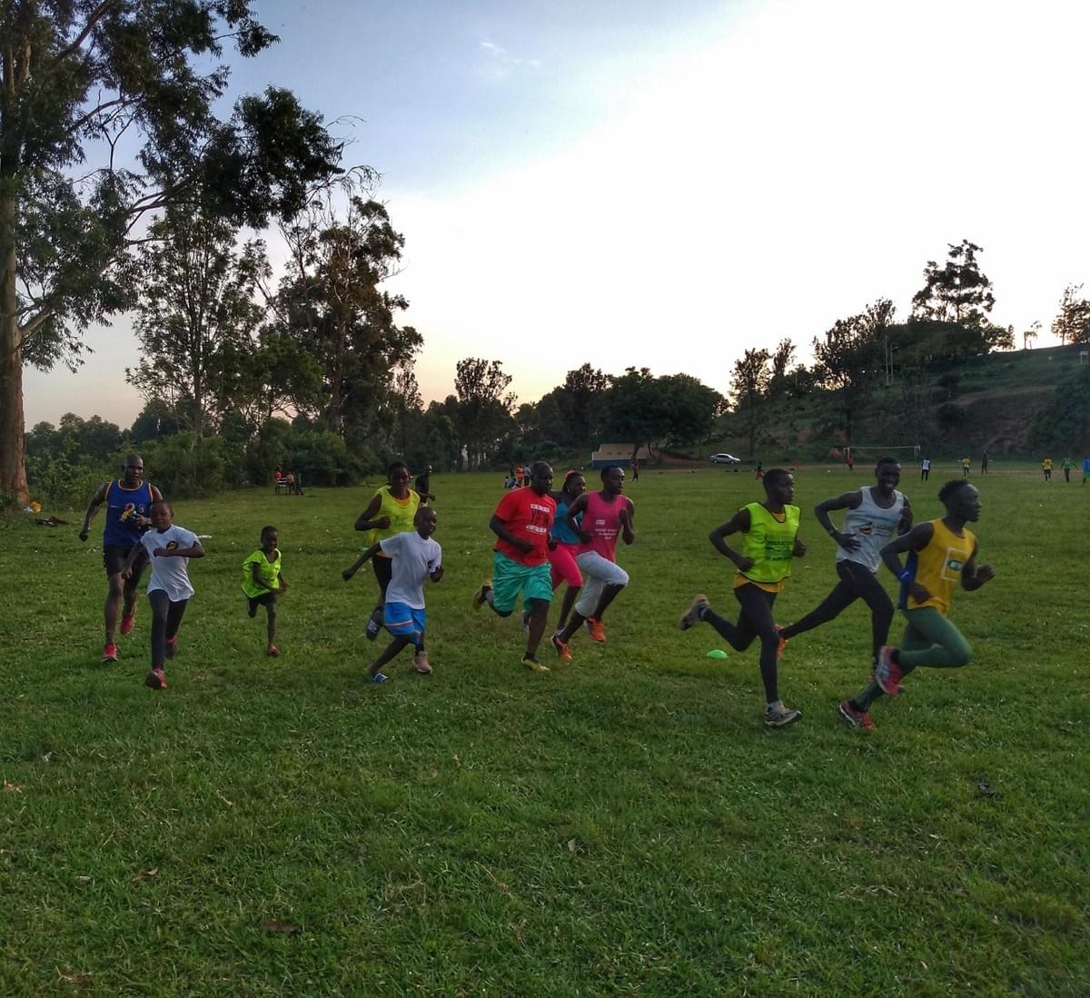 A group of local runners from young children to adults embark on an interval session on a sports field in Masaka, Uganda