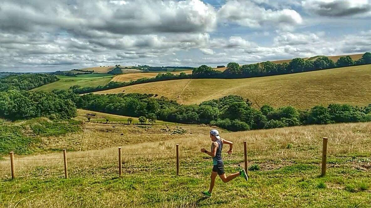 Running down a hilly trail on Dartmoor, UK. Rolling hills in the background.