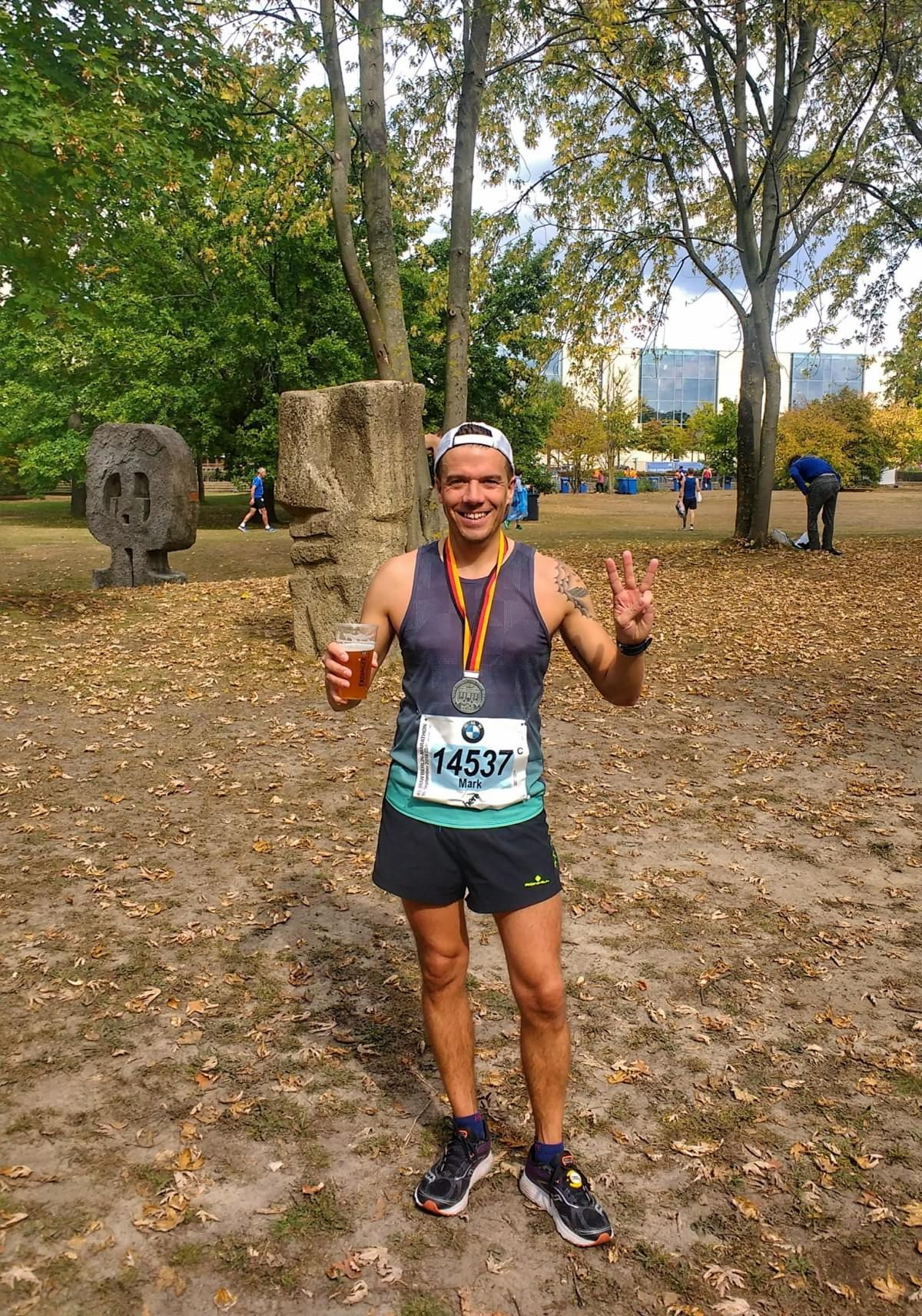 Berlin Marathon post-race medal and beer celebration in the Tiergarten