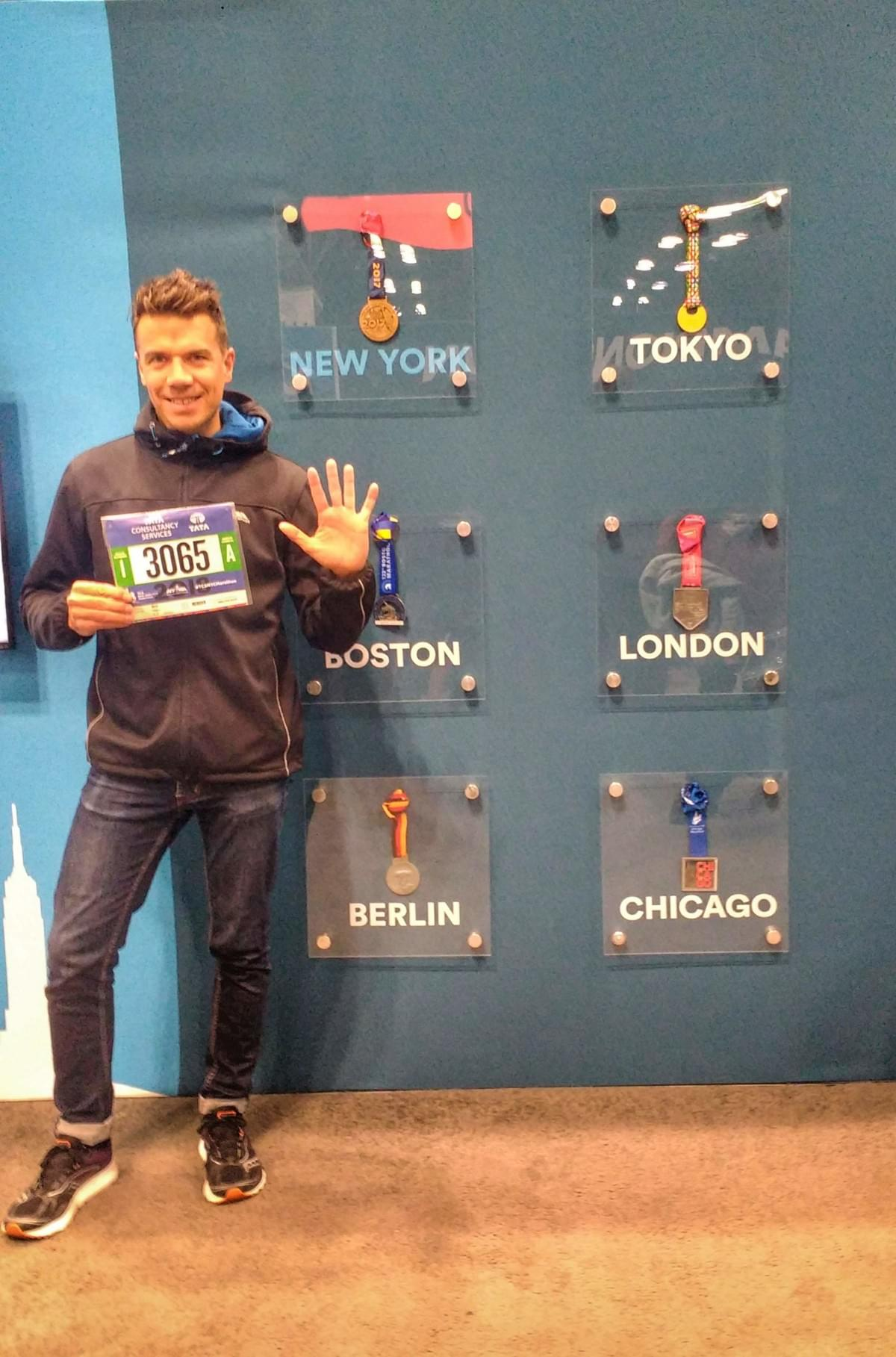 A runner holds his race number in front of the six world marathon major medals at the New York Marathon expo