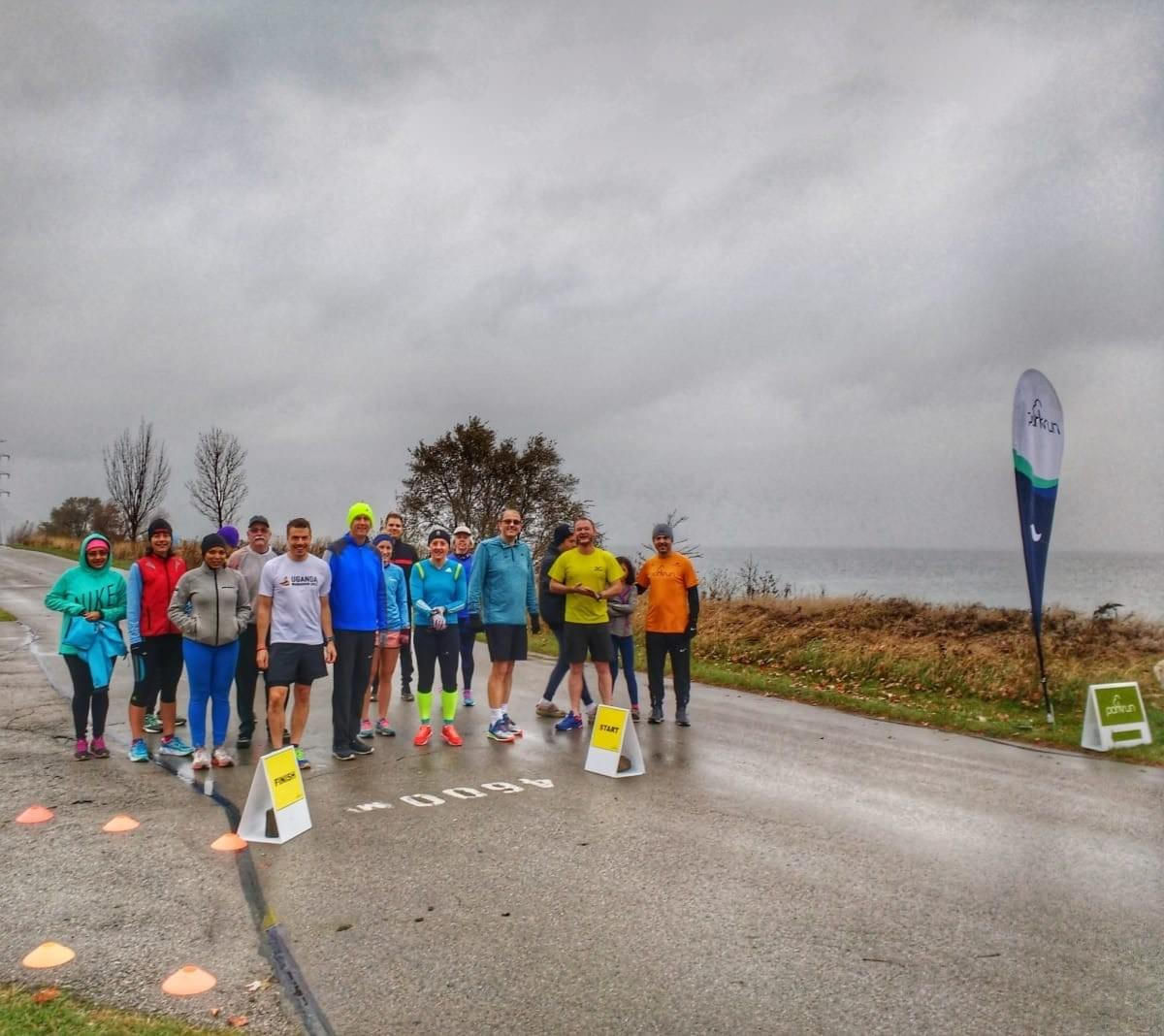 A group of well-wrapped runners gather at the start line of Beach Strip parkrun, Hamilton beside a cloudy Lake Ontario