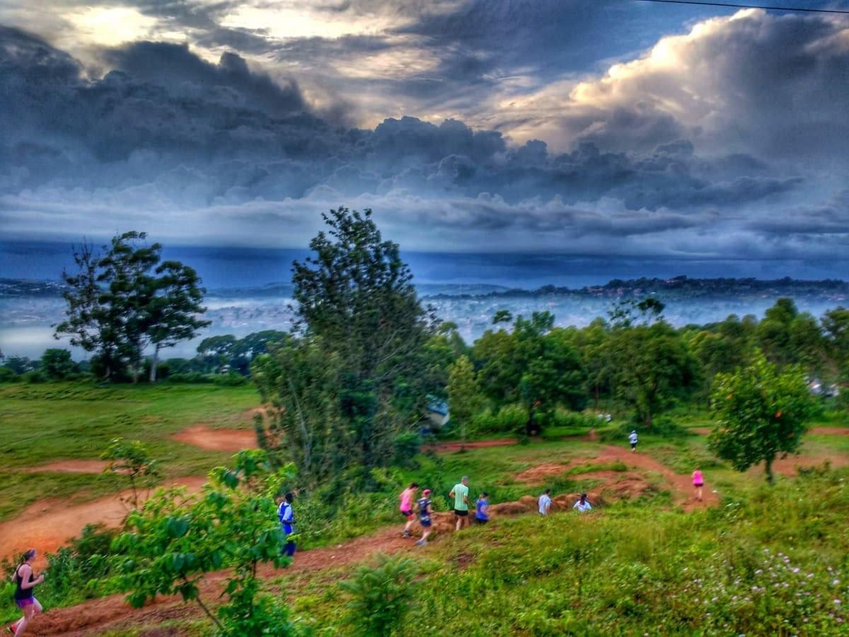 A group of Uganda Marathon 2018 runners descend on a dirt trail through trees during an early morning training run