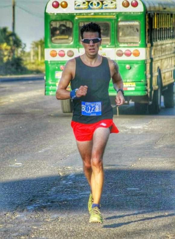 Running alongside a chicken bus during a race in El Salvador