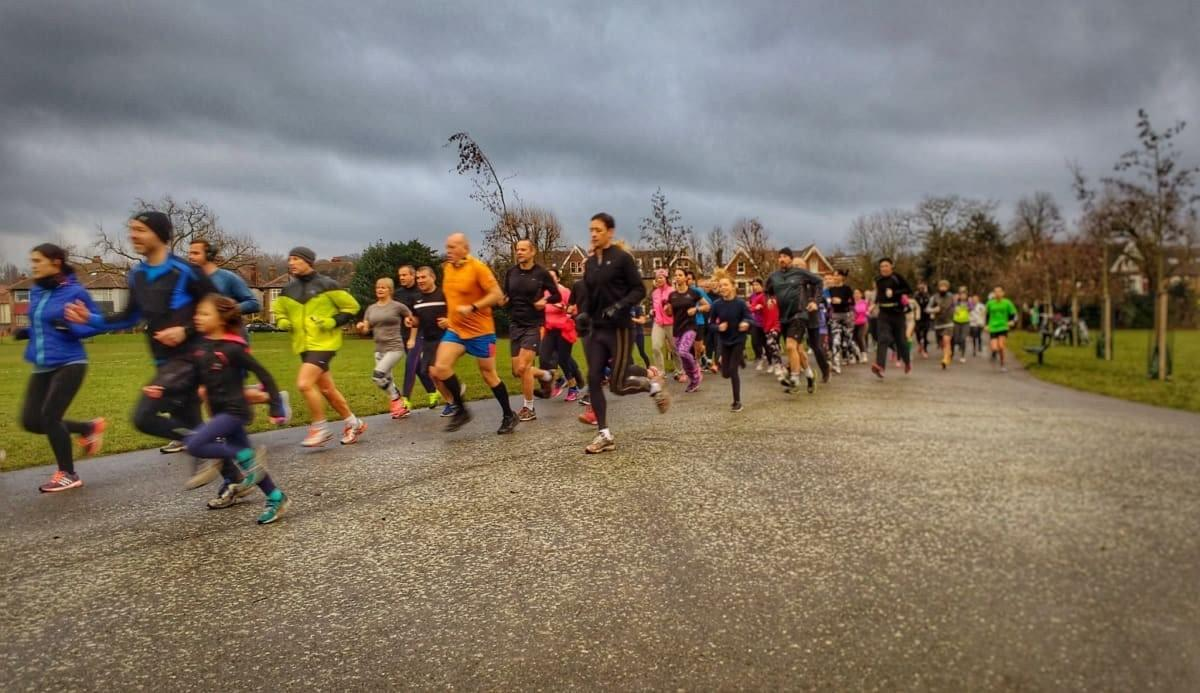A large group of runners of all ages sprint away at the start of Peckham parkrun in South London, UK