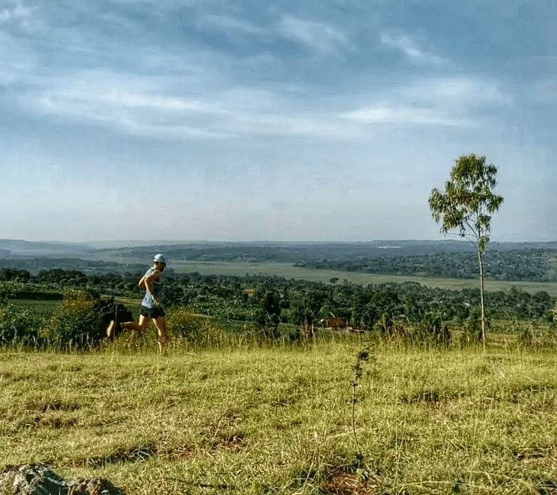 A Trail runner begins a descent from a ridge in Ndegeya, Uganda high above spectacular rural views in the background