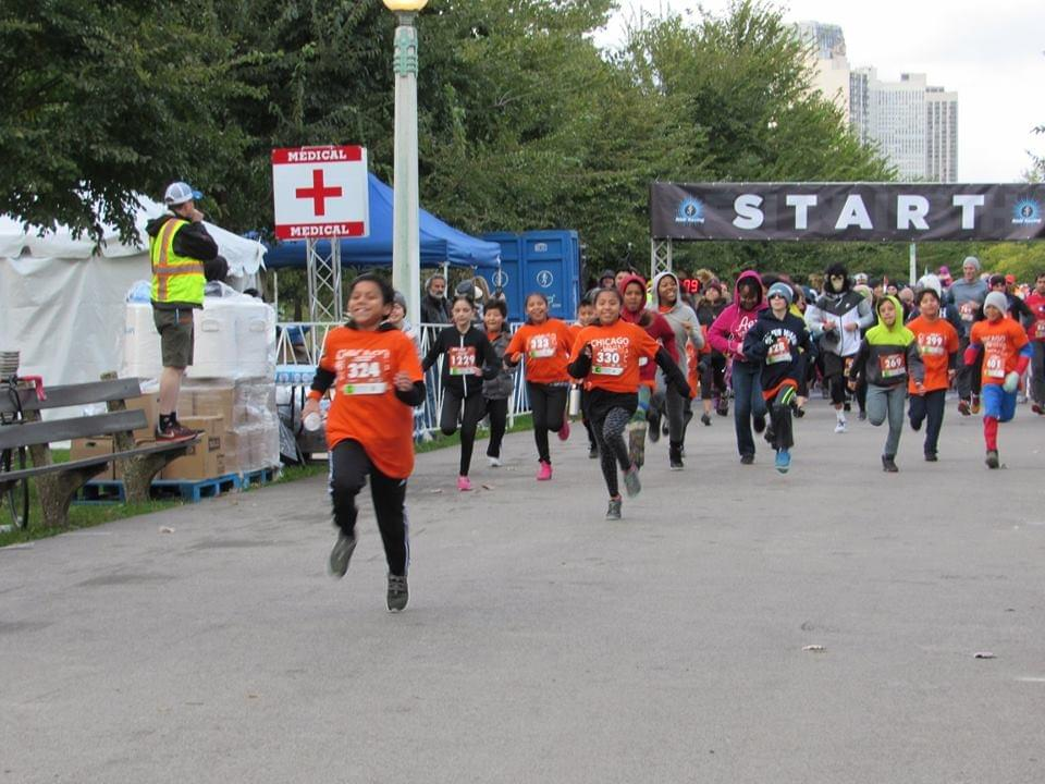 A group of young runners excitedly sprint away at the start of the 'Pumpkins in the Park' in Lincoln Park, Chicago