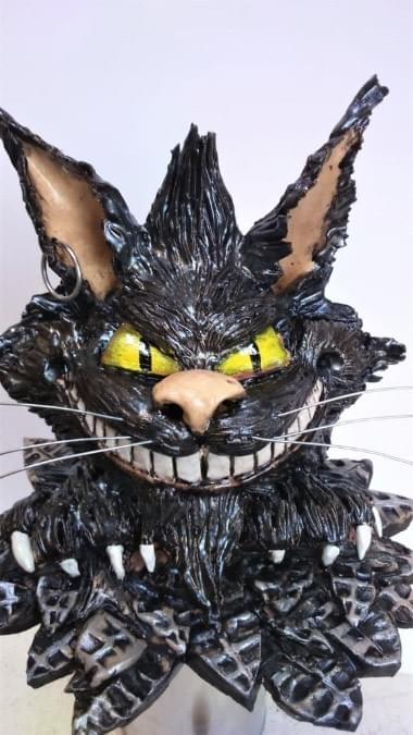 "'Oil' effect glaze on free standing Cheshire cat. Head is 7"" x 7"" and 8"" wide across leaf effect base. Earthenware clay"