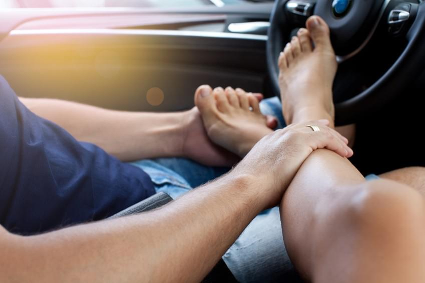 Man Touching Woman's Feet In Car