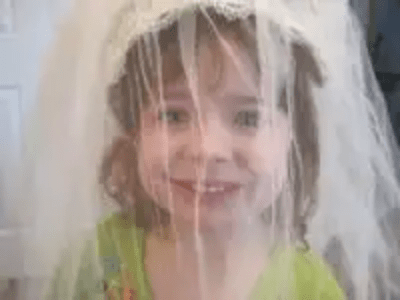 "Little Girl Playing ""Wedding"" In A Bride's Veil"