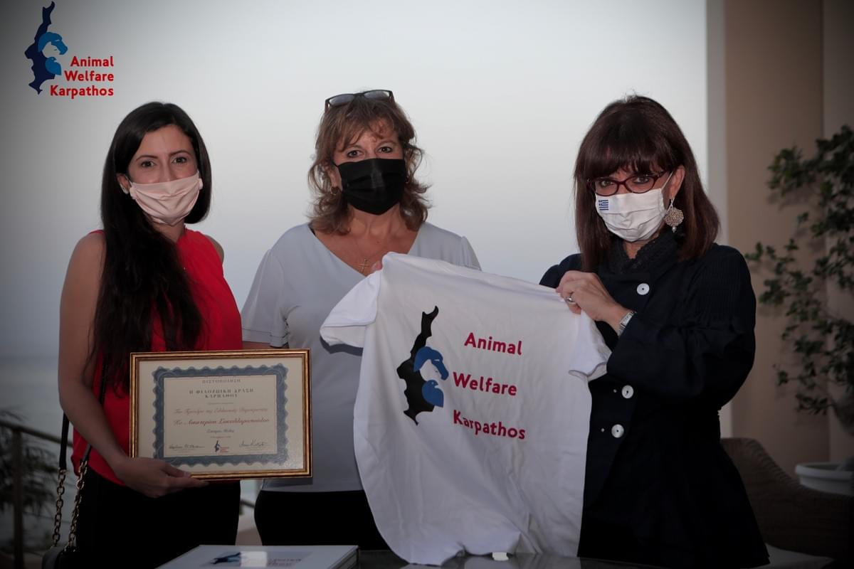 President of the Hellenic Republic, Katerina Sakellaropoulou being presented with a t-shirt and honorary certificate of membership with AWK