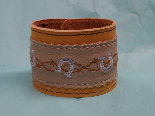 Leather bracelet with embroidered horse shoe design.